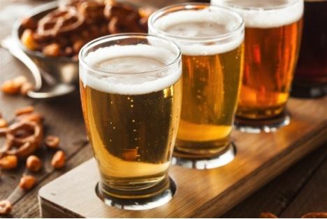 three glasses of beer and pretzels